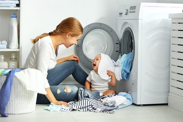 Baby and mother folding clothes by the dryer
