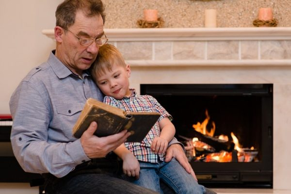 grandfather to his grandson reading a book by the fireplace